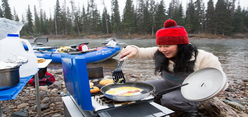 girl-cooking-beside-river